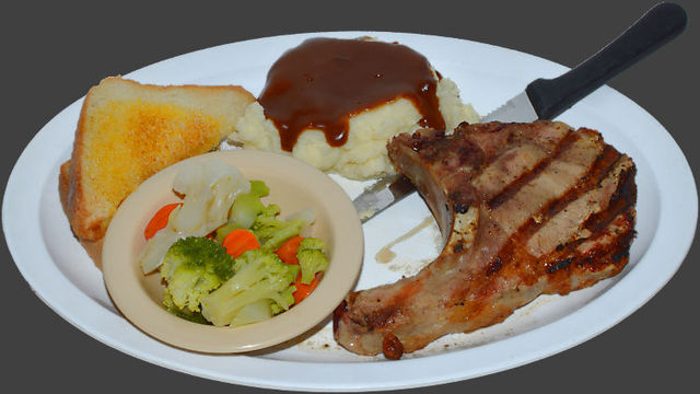 Hand-sliced 6 oz. chop. Served with mashed potatoes, brown gravy, vegetables and Texas toast. - Bone-In Pork Chop Lunch at Ranch House Grille