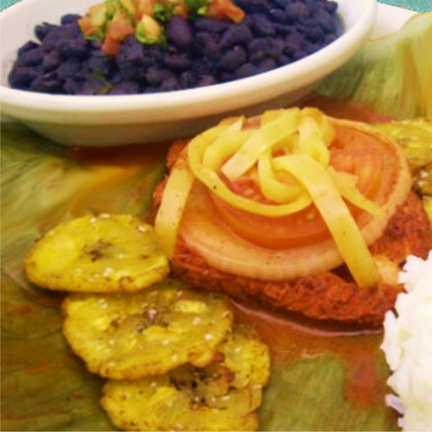 new to the menu, this salmon is baked in a banana leaf and served with plantains, beans and rice - pescado en macum at Picante