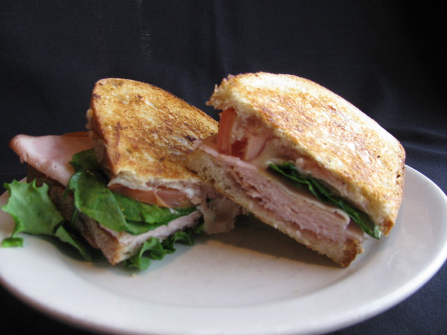 A mound of sliced turkey, fresh baby spinach, a slice of tomato, melted mozzarella and a strawberry  - Turkey Panini at Chicago Blu Grill and Bar