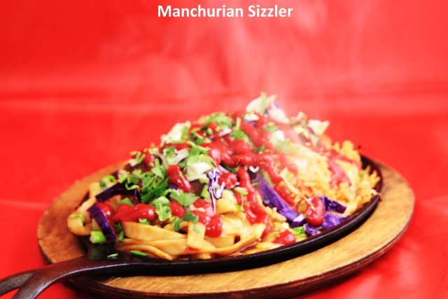 Vegi Manchurian Balls, onions, bell peppers, cabbage, cheese served on Hakka Noodles and Fried Rice  - Manchurian Sizzler at Standard Sweets and Snacks