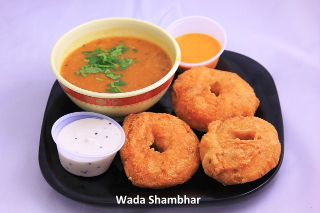 A lentil and rice fritter with cumin and green chilli  served with Sambhar - Wada Sambhar at Standard Sweets and Snacks