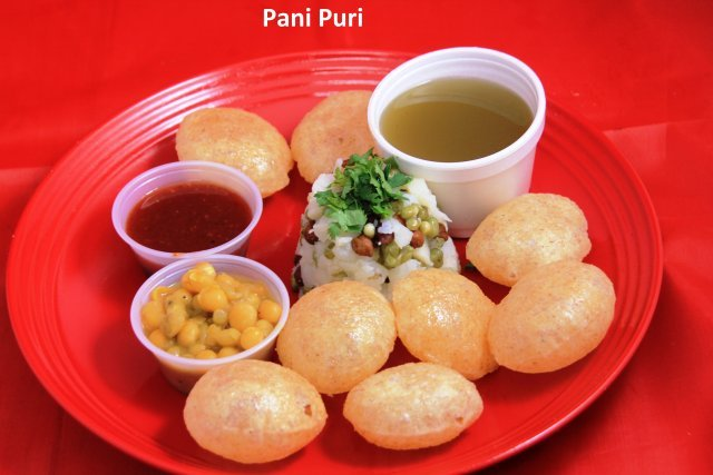 Crispy puri served with potatoes, moong, channa, ragdo, spicy mint water, and sweet chutney  - Pani Puri at Standard Sweets and Snacks